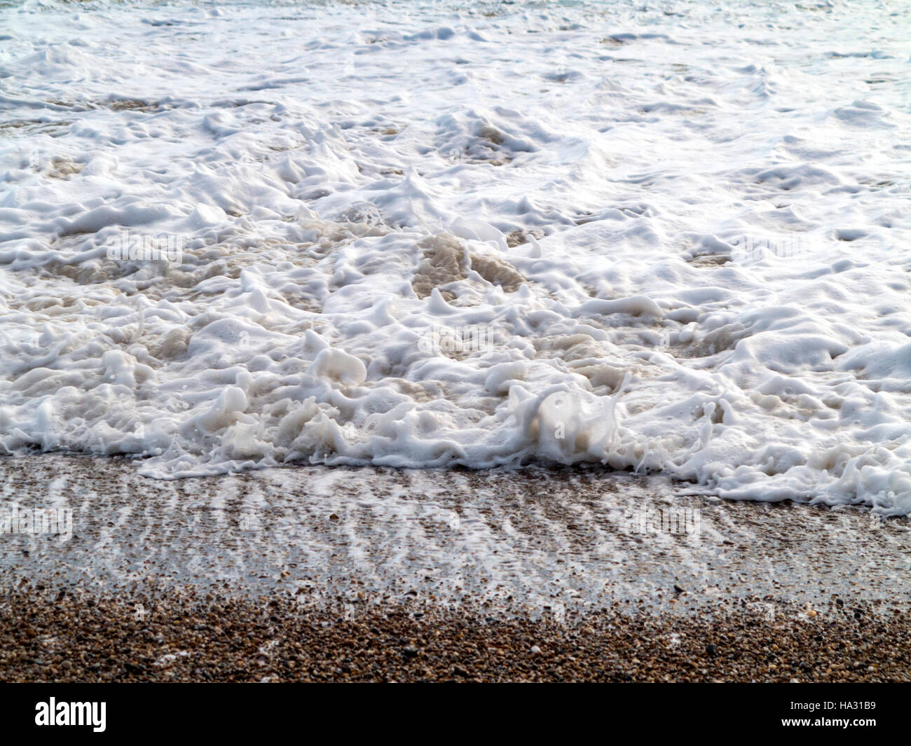 Tidal froth on a pebble beach shoreline during heavy seas - Stock Image