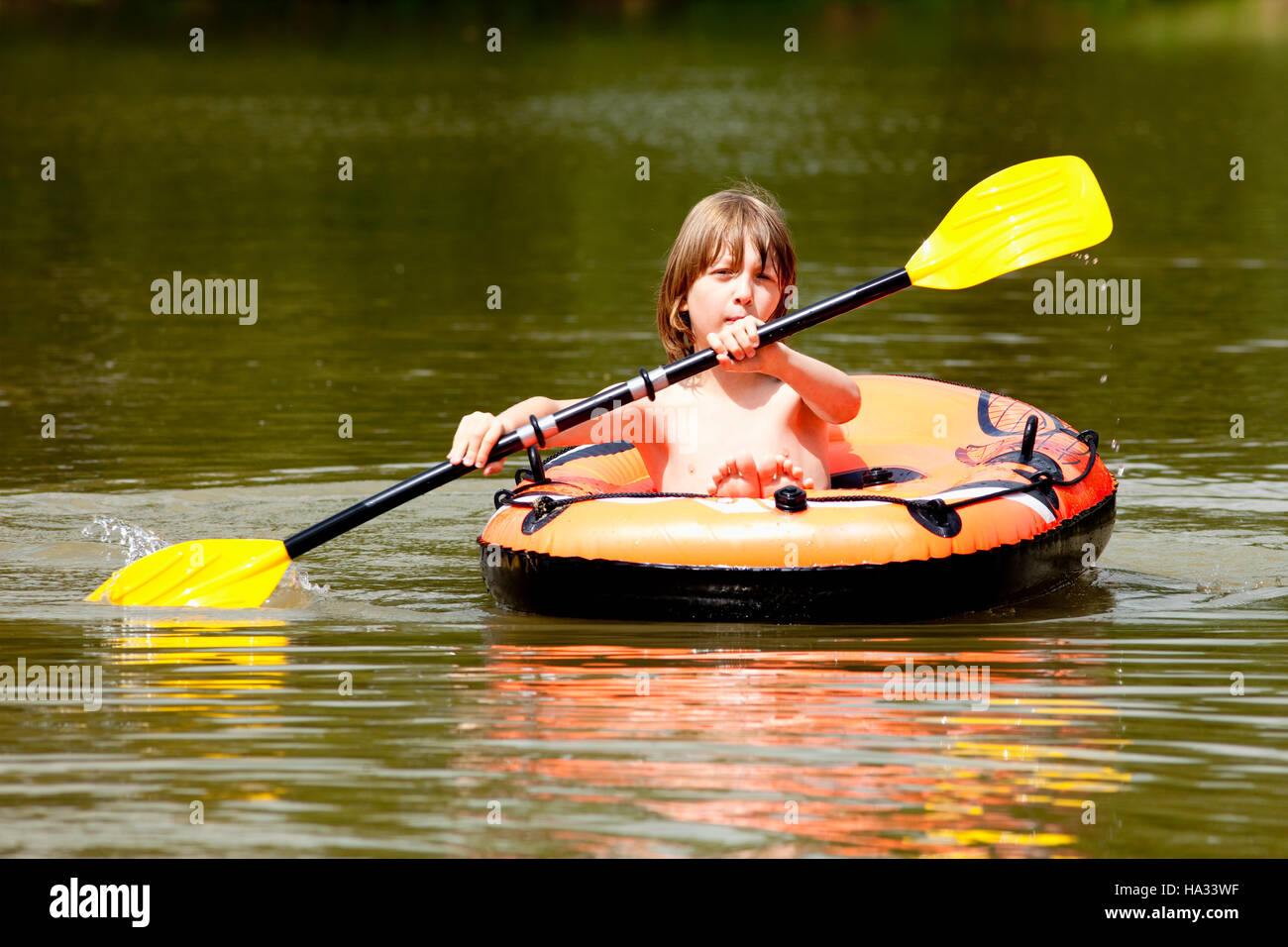 Boy with Blond Hair Paddles Inflatable Rubber Boat - Stock Image