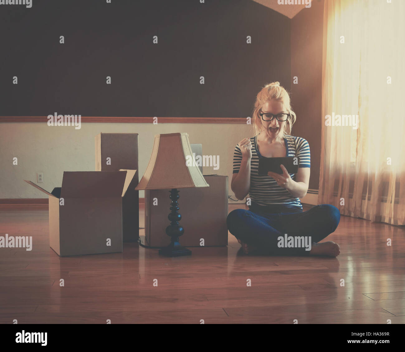 A girl is sitting in an empty room with boxes. She is holding a technology tablet for an interior design or moving - Stock Image