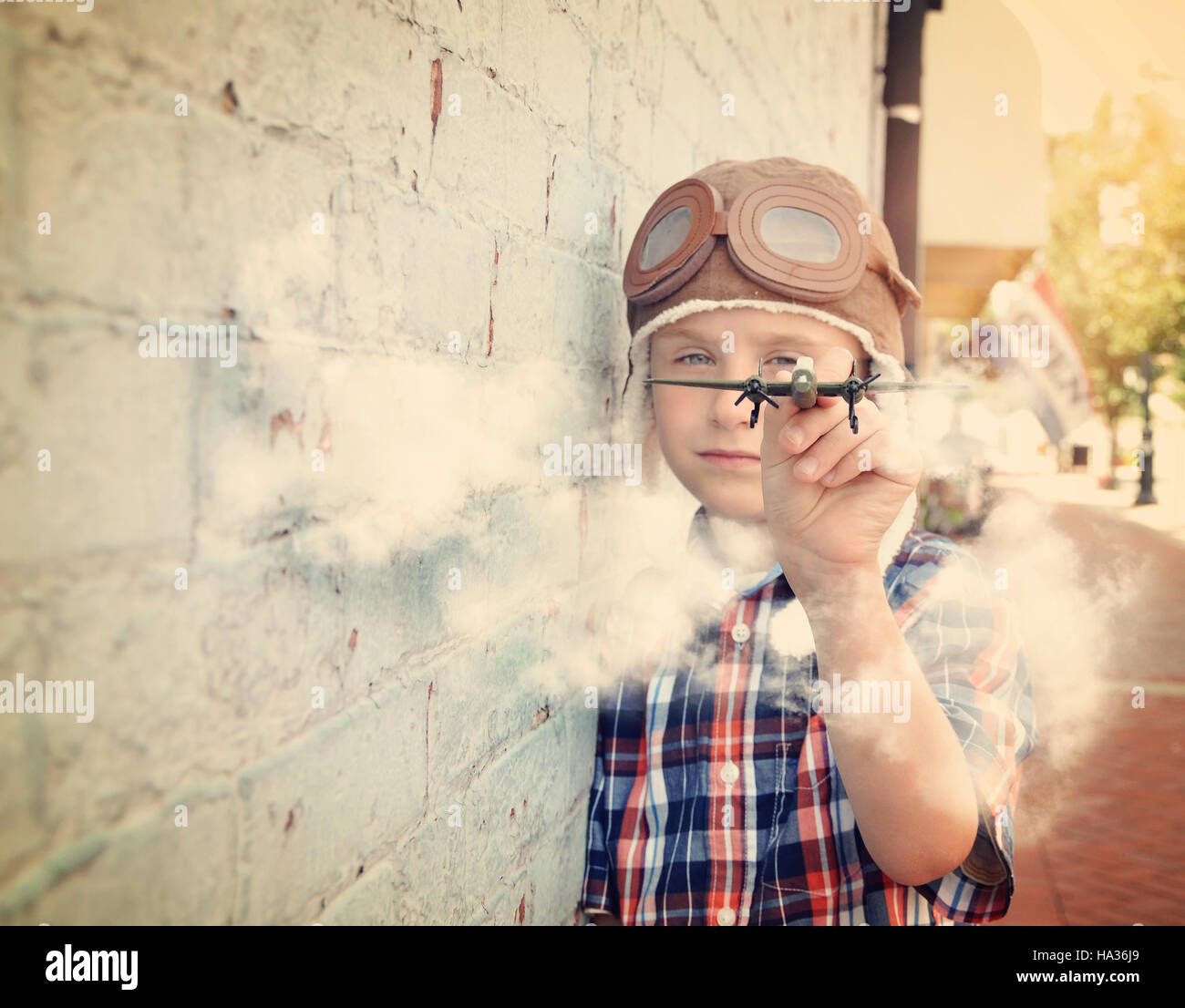 A young boy is pretending to be a pilot and playing with an airplane toy against a brick wall for a dream or career Stock Photo