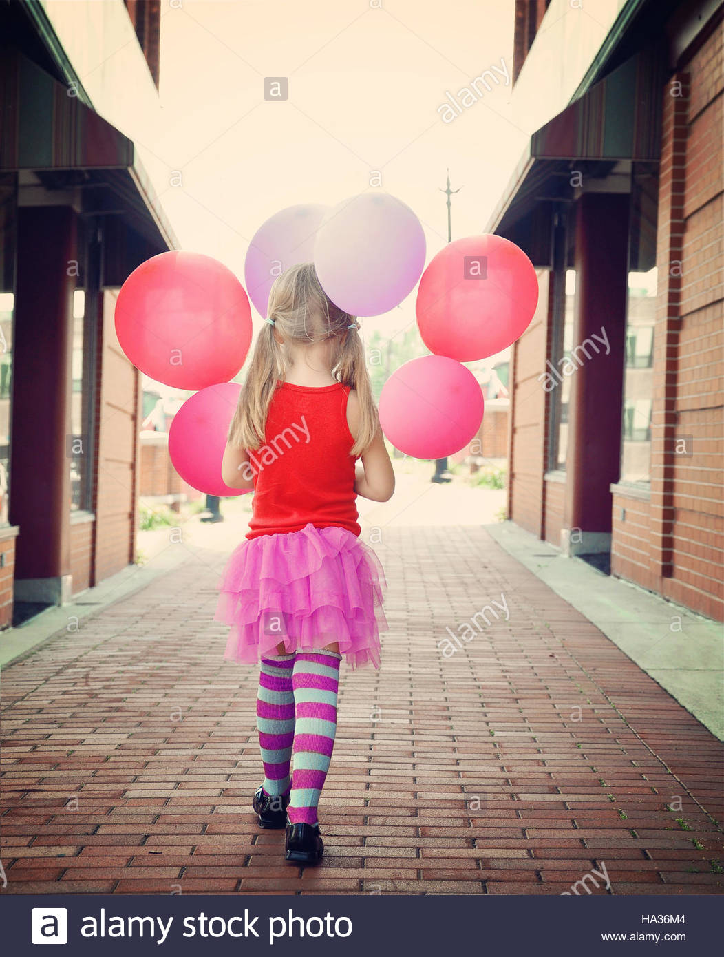 A little girl is holding colorful balloons walking down a brick road outside for a happiness or freedom concept. - Stock Image