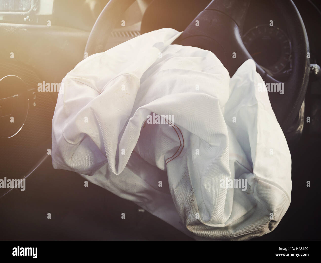 A front car airbag has deflated in a steering wheel from an accident. Use it for a safety or insurance concept. - Stock Image
