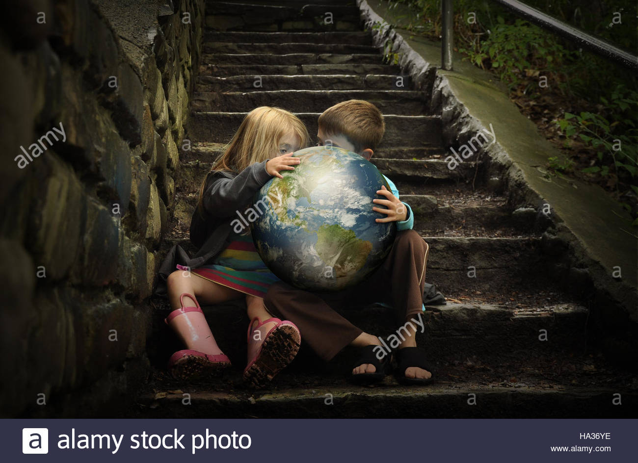 Children are holding the planet earth on wet dark stairs for a weather or season concept about the environment. - Stock Image