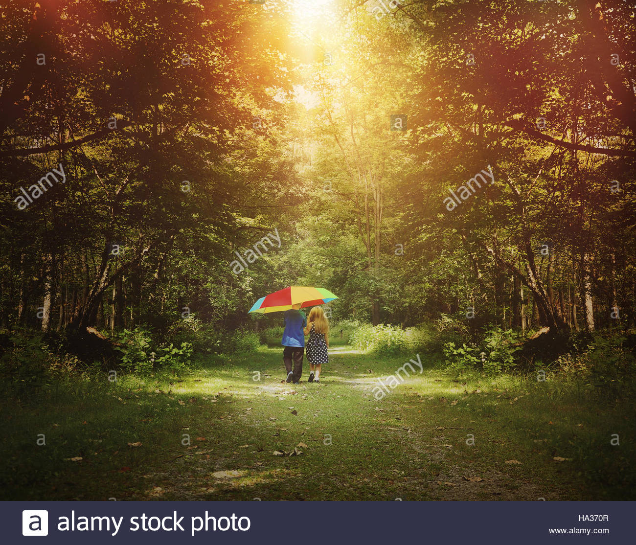 Two children are walking down a sunshine trail in the woods holding a rainbow umbrella for a friendship, hope or - Stock Image