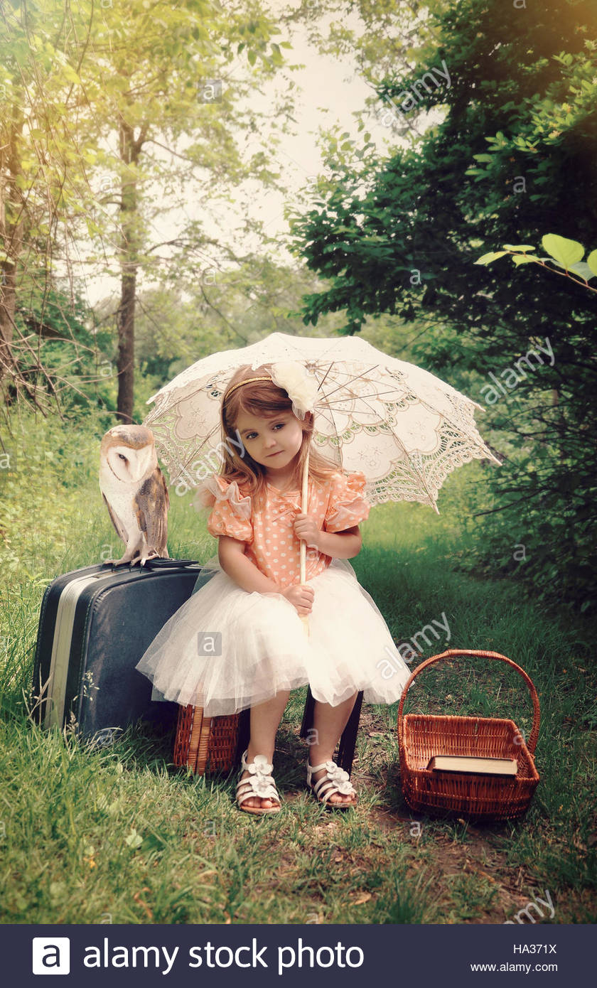 Beautiful portrait of a little girl with an umbrella and pet barn owl in the forest with a vintage look for a imagination - Stock Image