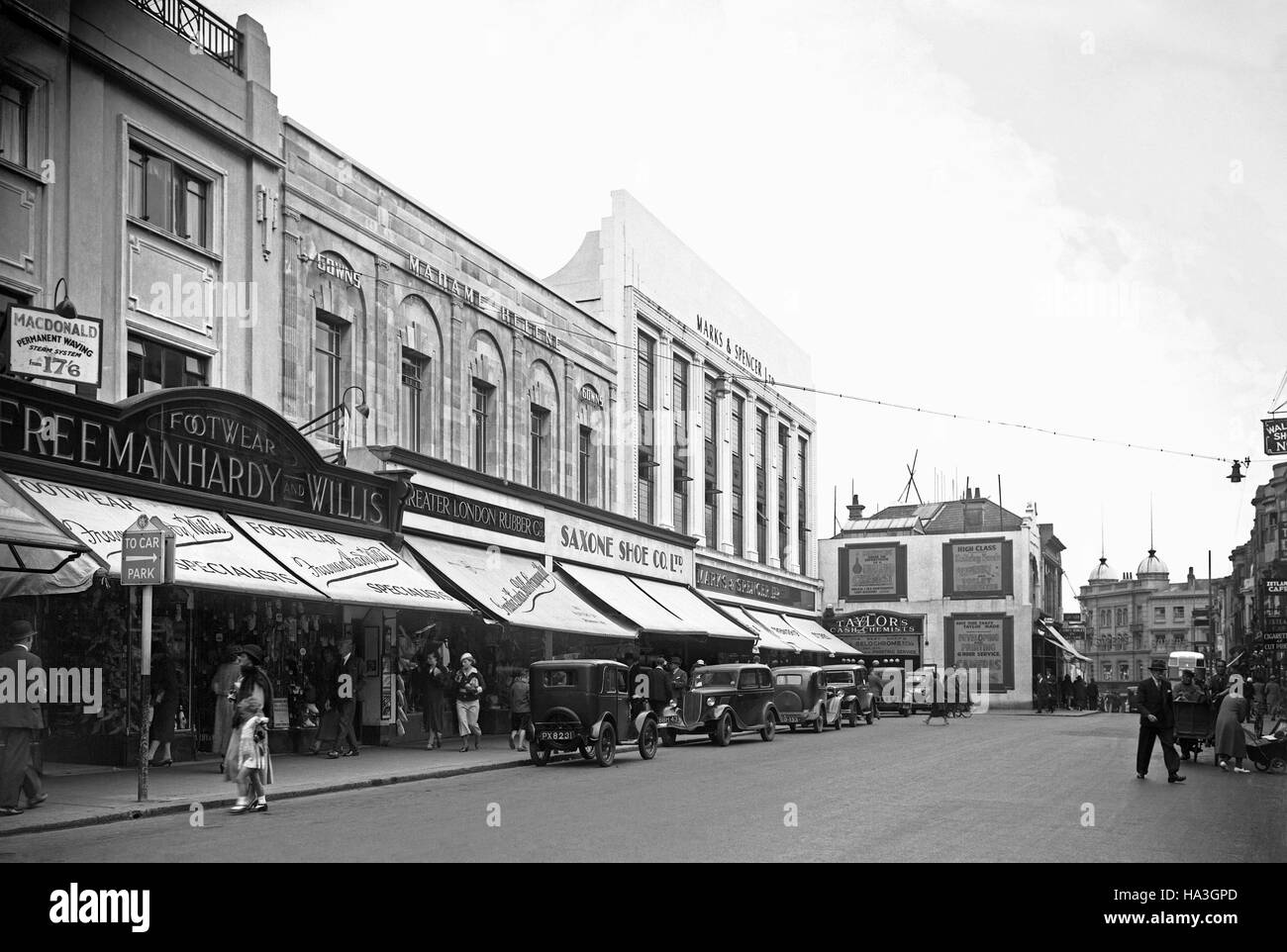 Shops and shoppers at the eastern end of Western Road, Brighton, East Sussex, England, c.1935 - shops include Marks - Stock Image