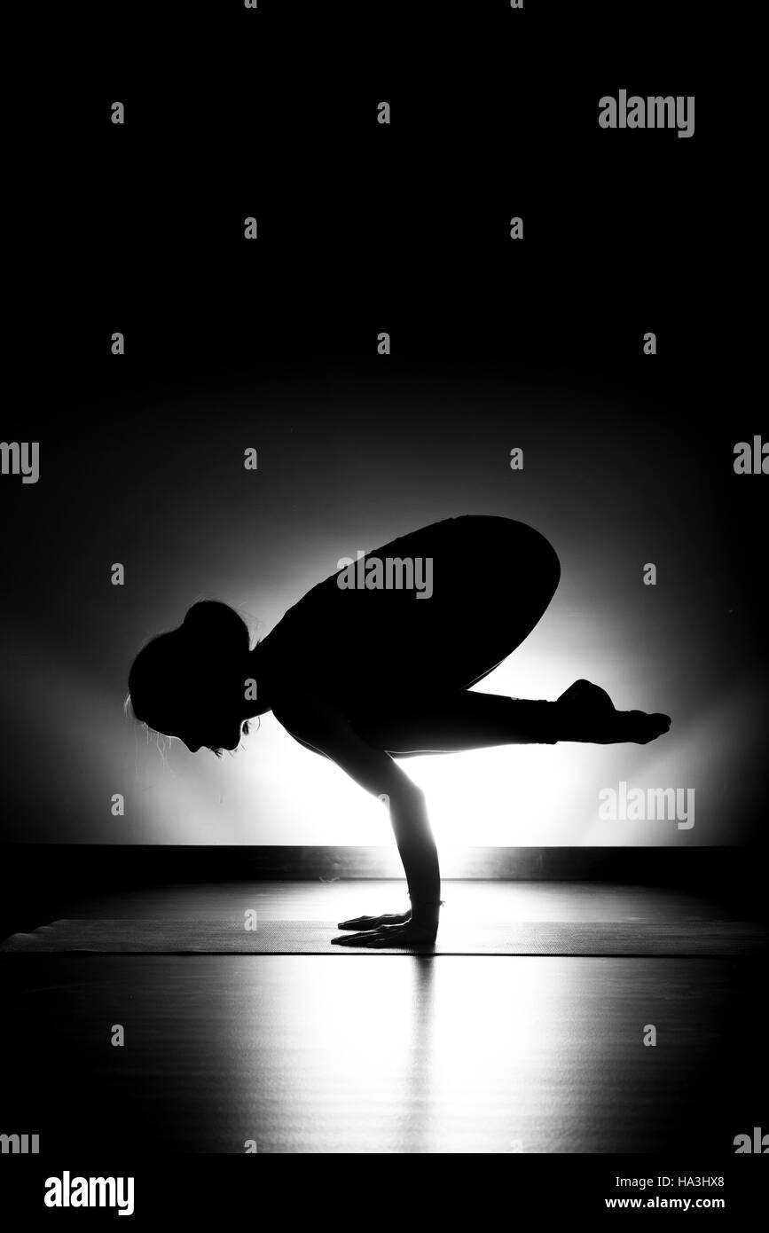 Woman doing yoga crow pose silhouette black and white in studio - Stock Image
