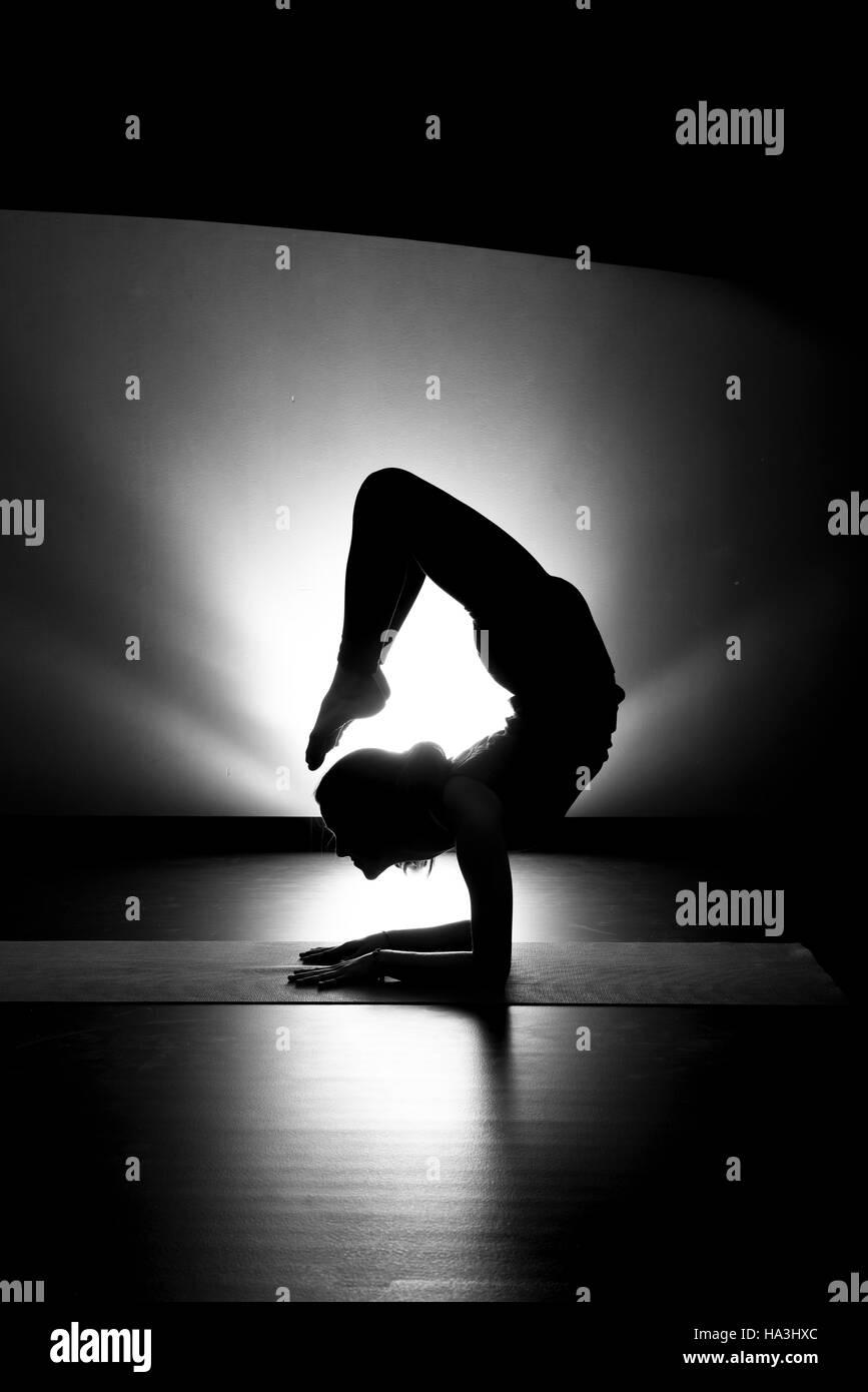 Woman doing yoga scorpion pose silhouette black and white in studio - Stock Image