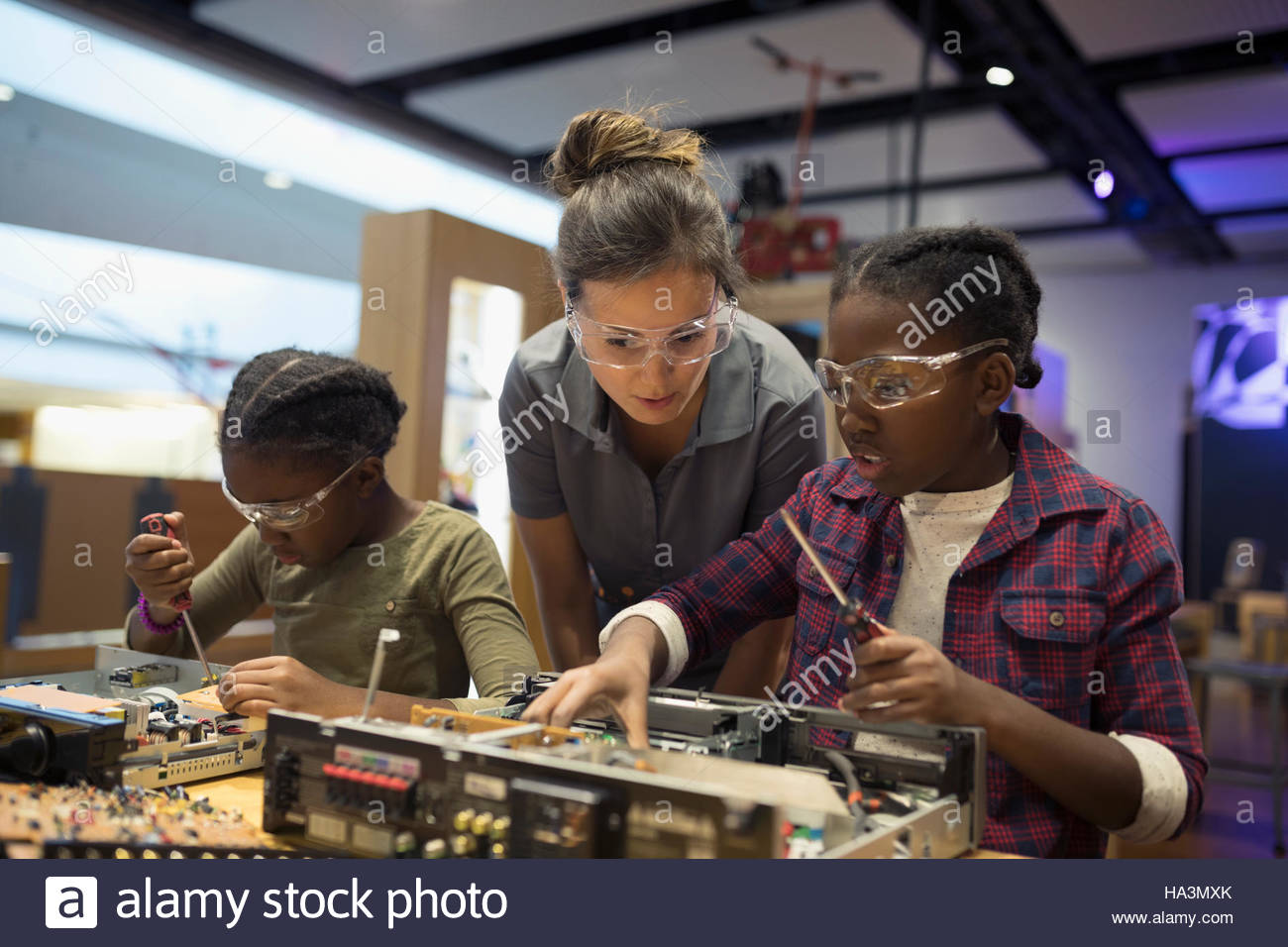 Scientist watching twin sisters assembling electronics in science center - Stock Image