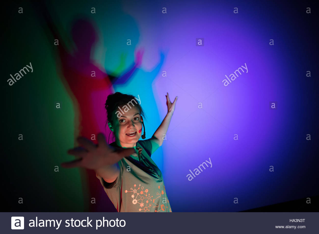Woman casting multicolor shadows on projection screen in science center theater Stock Photo