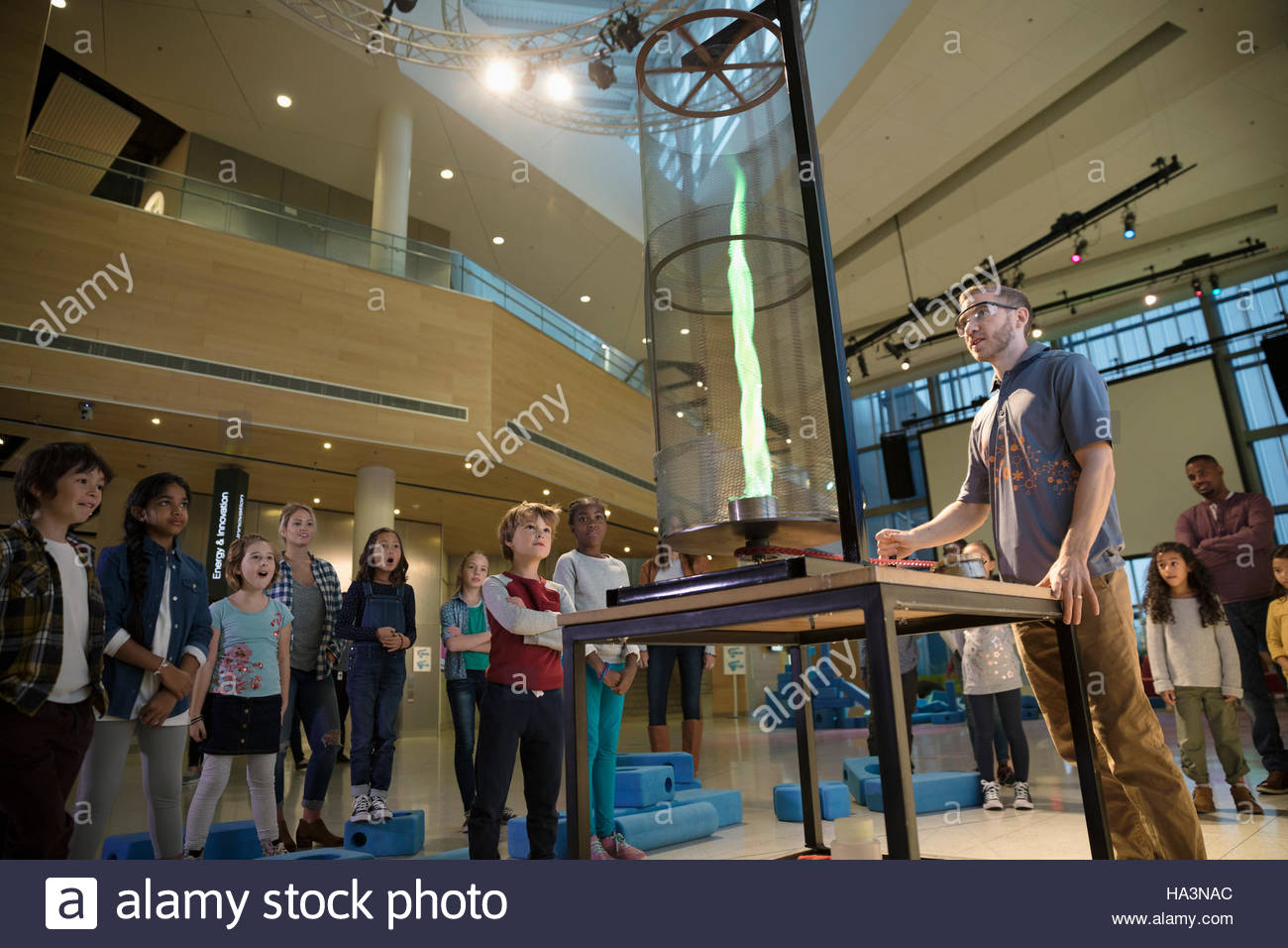 Children watching scientist conducting fire experiment demonstration - Stock Image