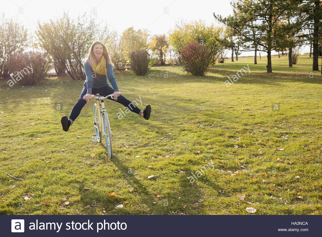 Playful woman riding bicycle in sunny autumn park - Stock Image