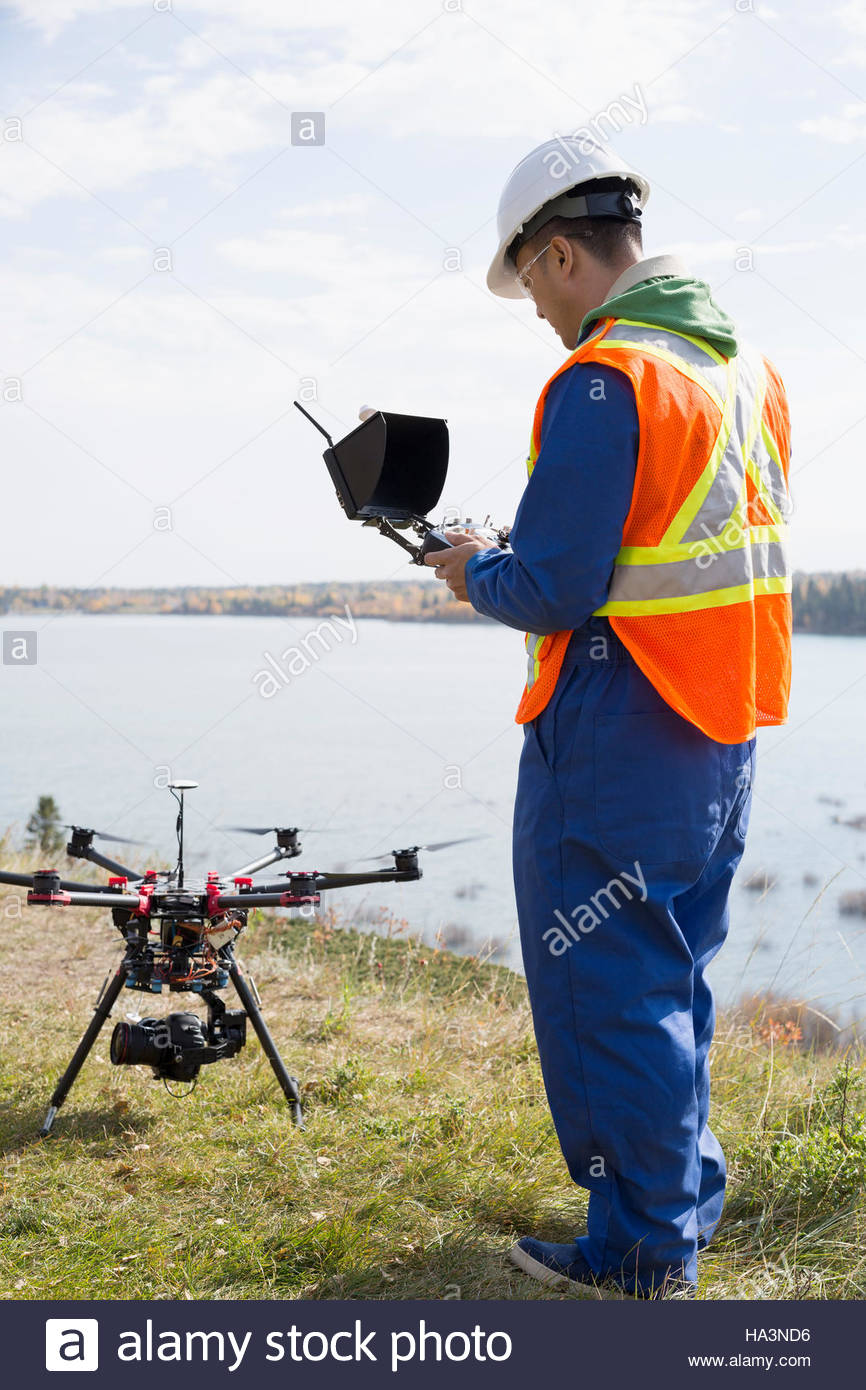 Surveyor with drone equipment at sunny lakeside - Stock Image