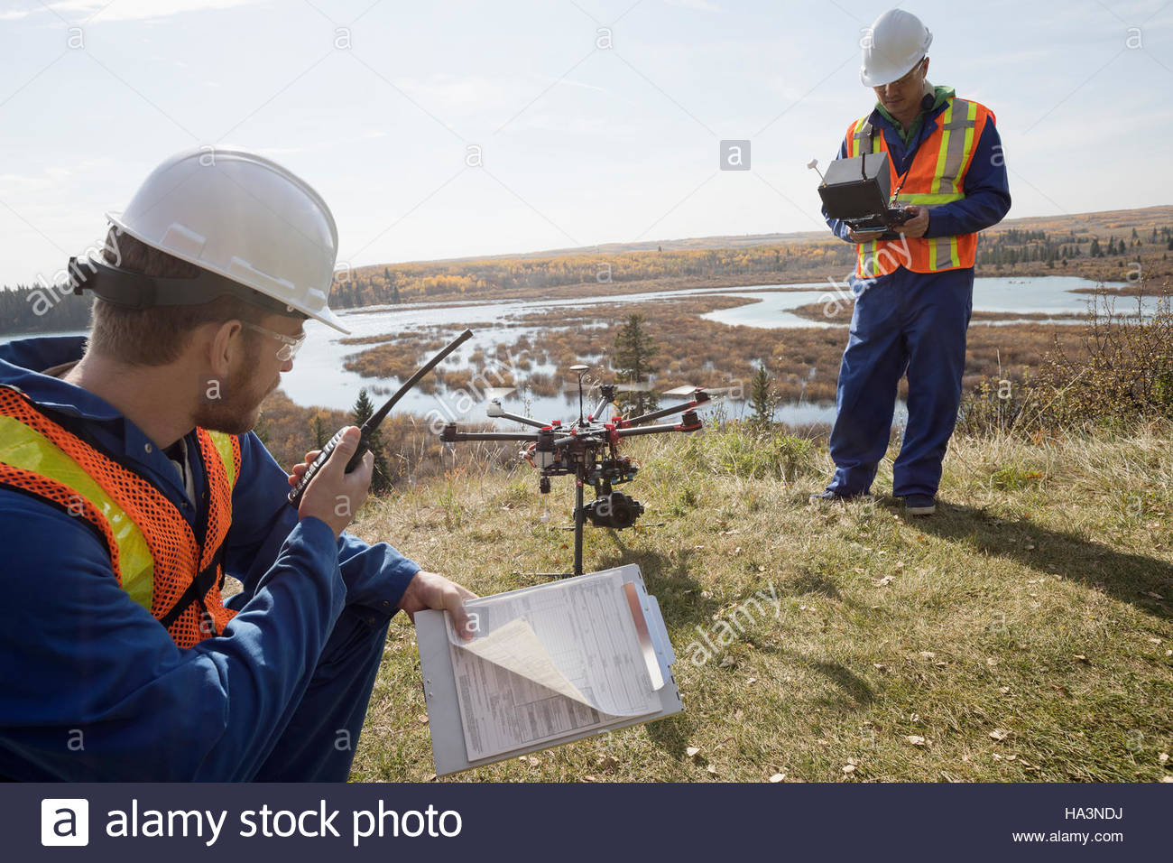 Surveyors with drone equipment and walkie-talkie on sunny hilltop overlooking lake - Stock Image