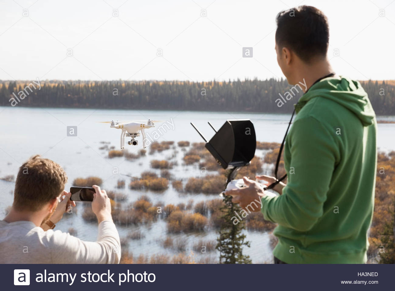 Male friends with drone equipment and camera phone overlooking lake - Stock Image