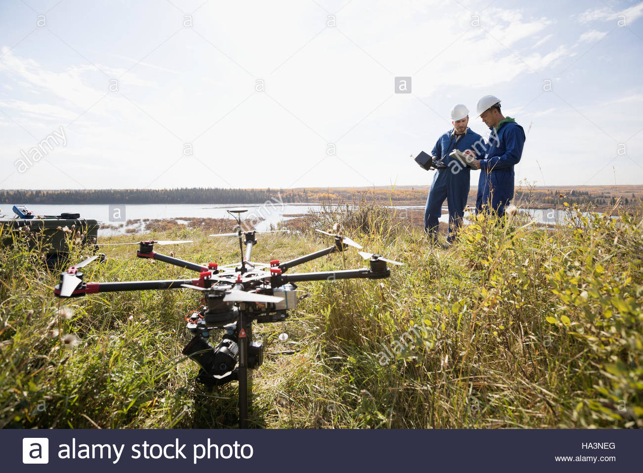 Surveyors with drone equipment on sunny hilltop overlooking lake - Stock Image