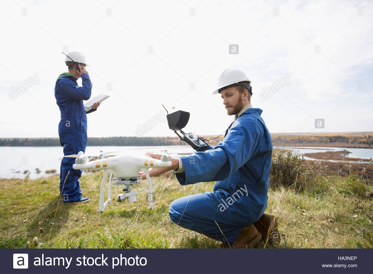Surveyors with drone equipment on hill overlooking lake - Stock Image