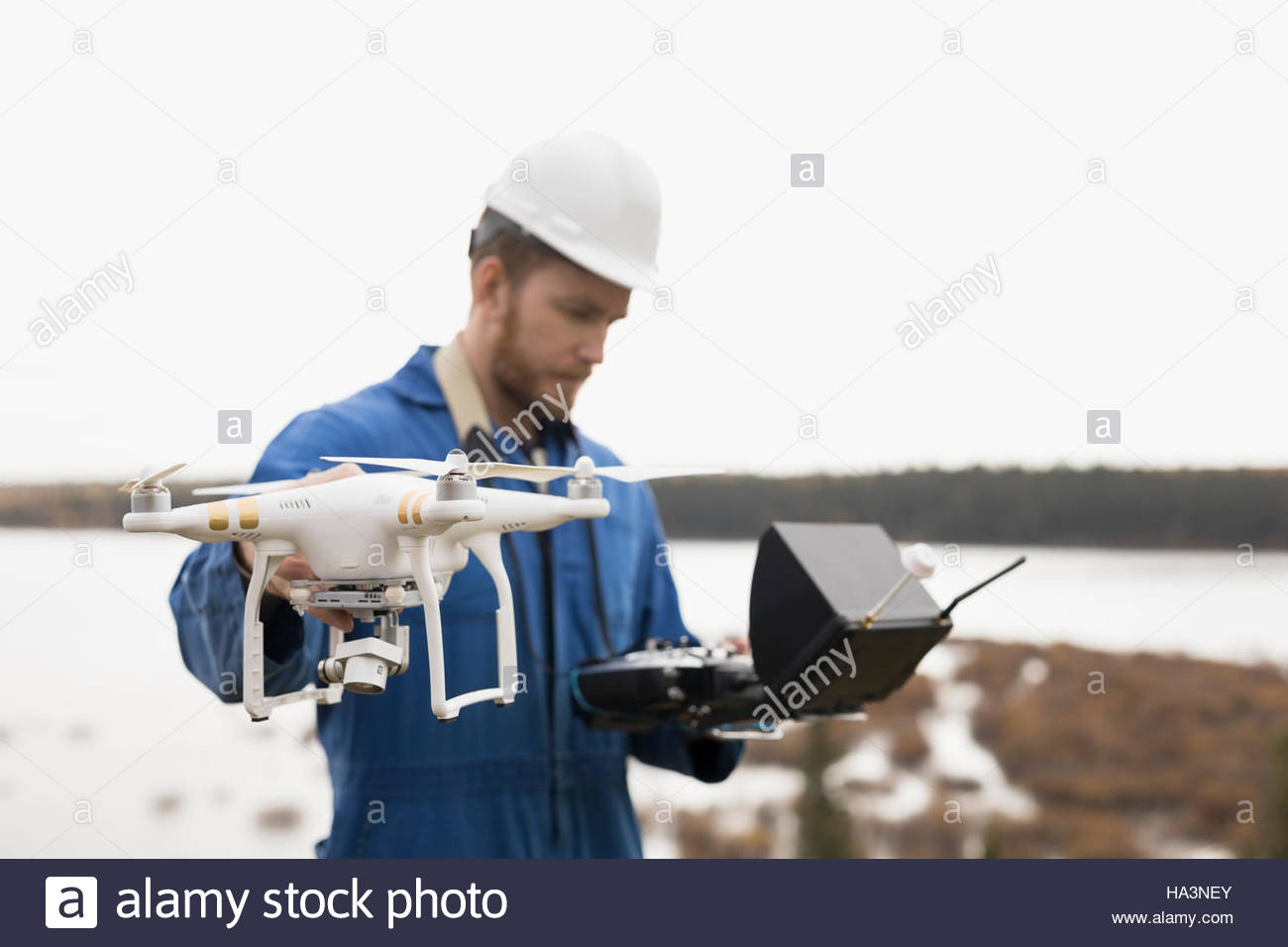 Surveyor with drone equipment at lakeside - Stock Image
