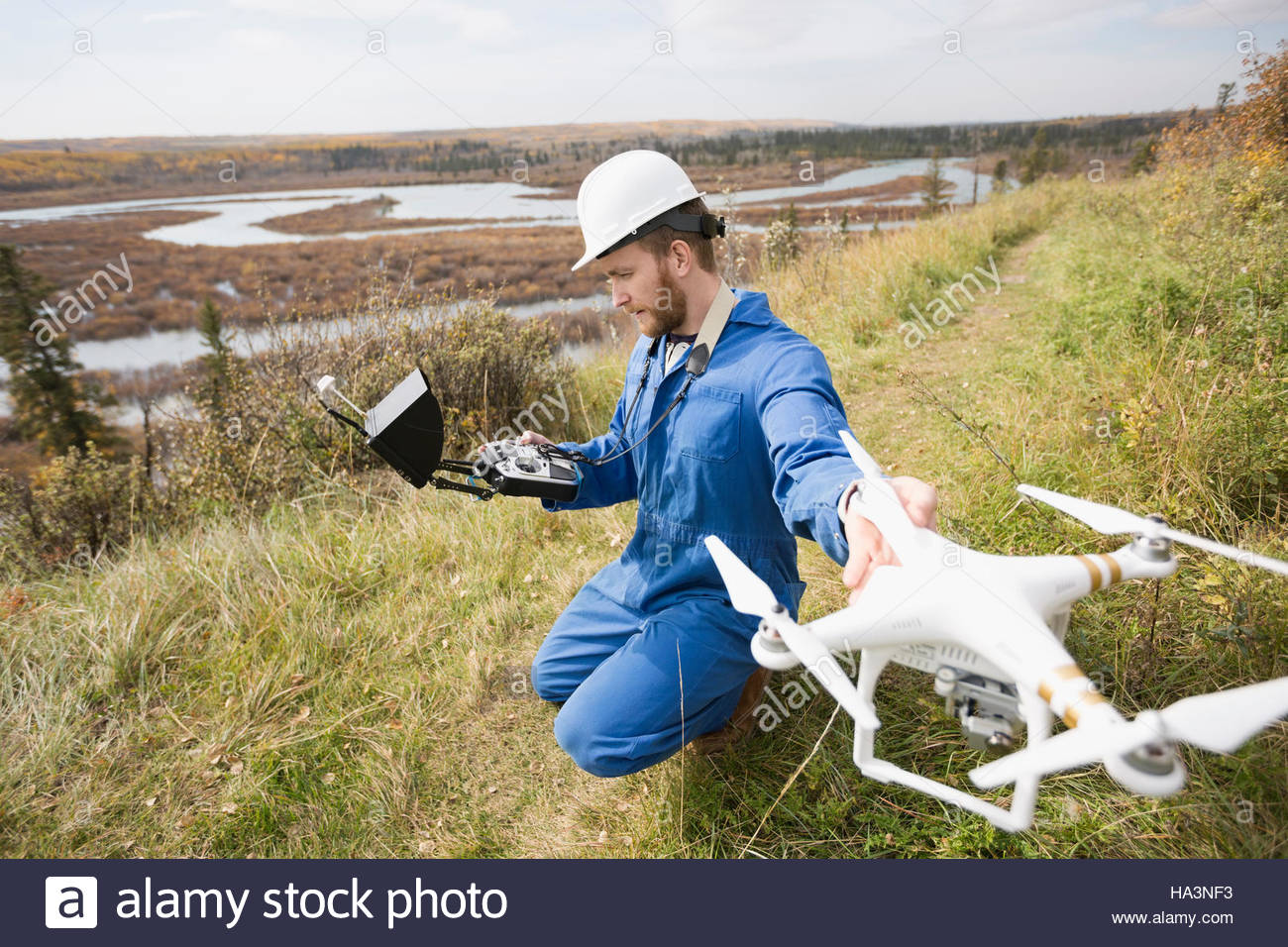 Surveyor with drone equipment on hillside - Stock Image