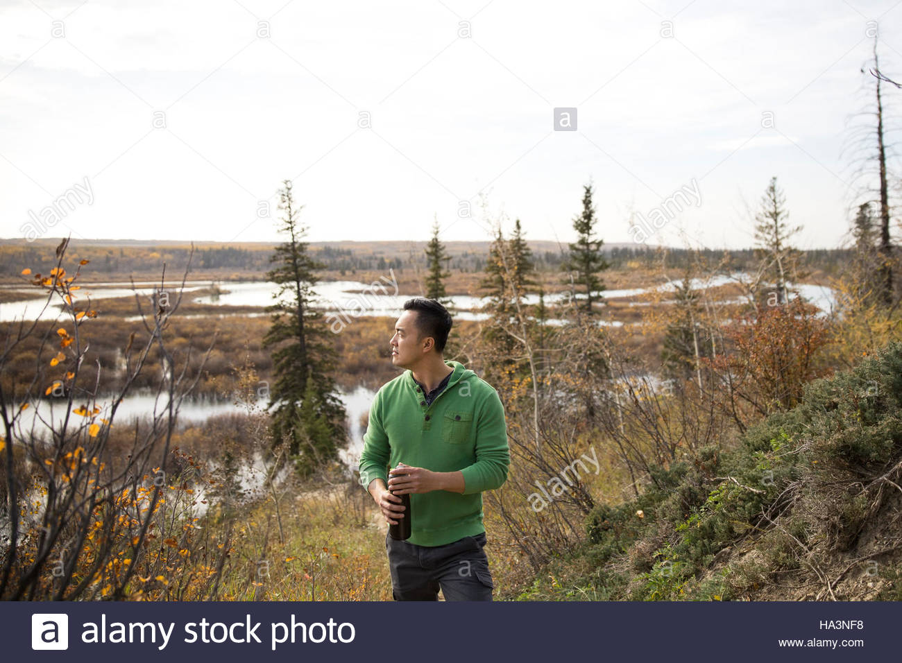 Man with water bottle hiking looking away at autumn lakeside - Stock Image