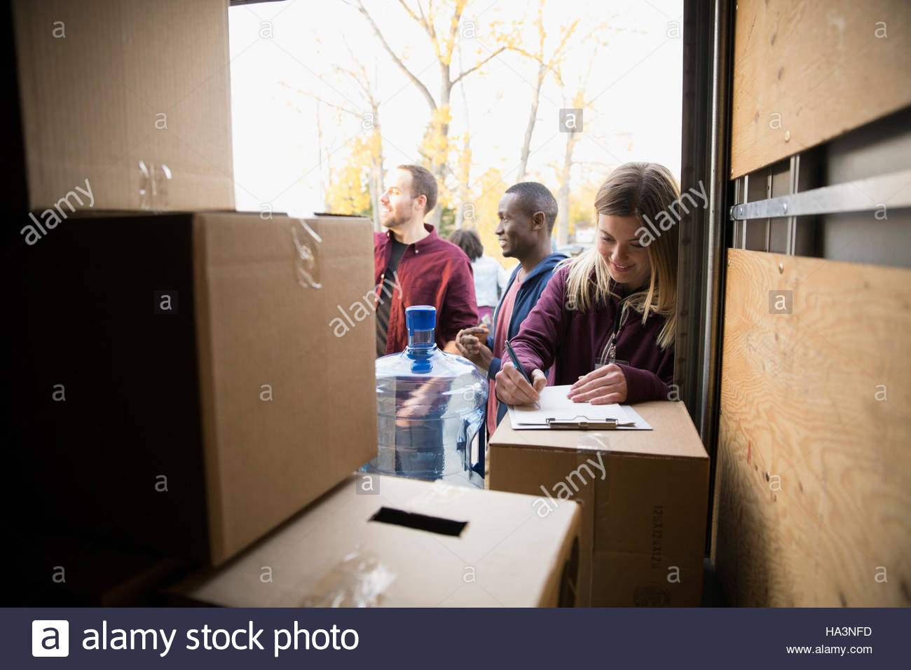 Volunteers at back of truck with cardboard boxes - Stock Image