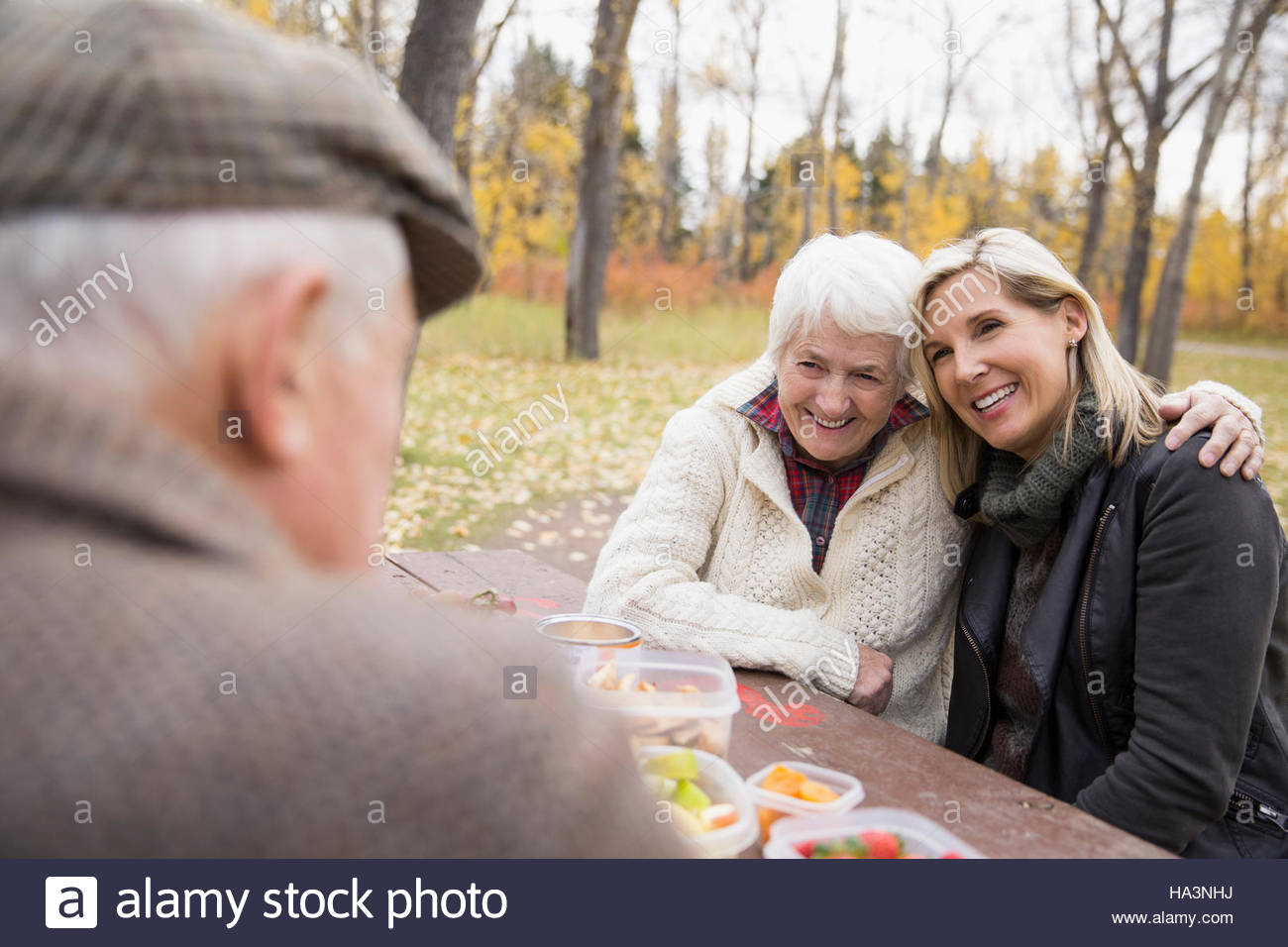 Mother and daughter hugging enjoying picnic at table in autumn park - Stock Image