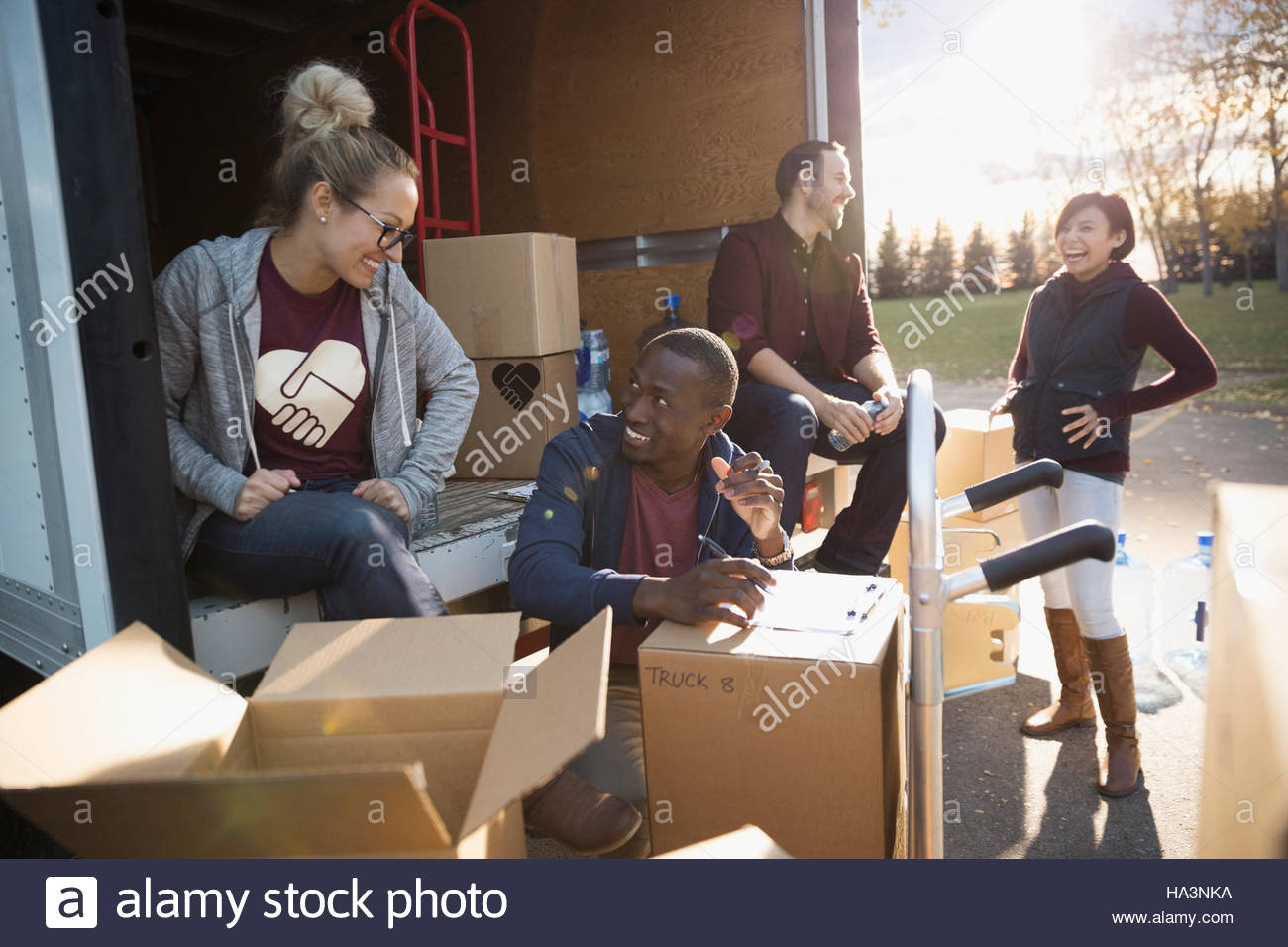 Volunteers talking among cardboard boxes at back of truck - Stock Image