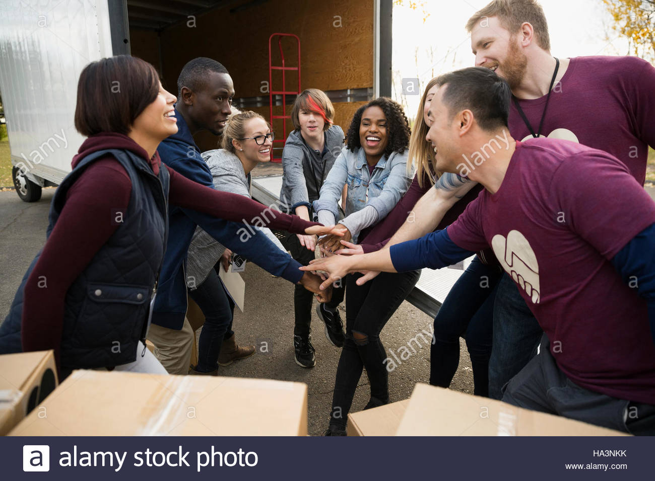 Enthusiastic volunteers joining hands in huddle outside truck - Stock Image