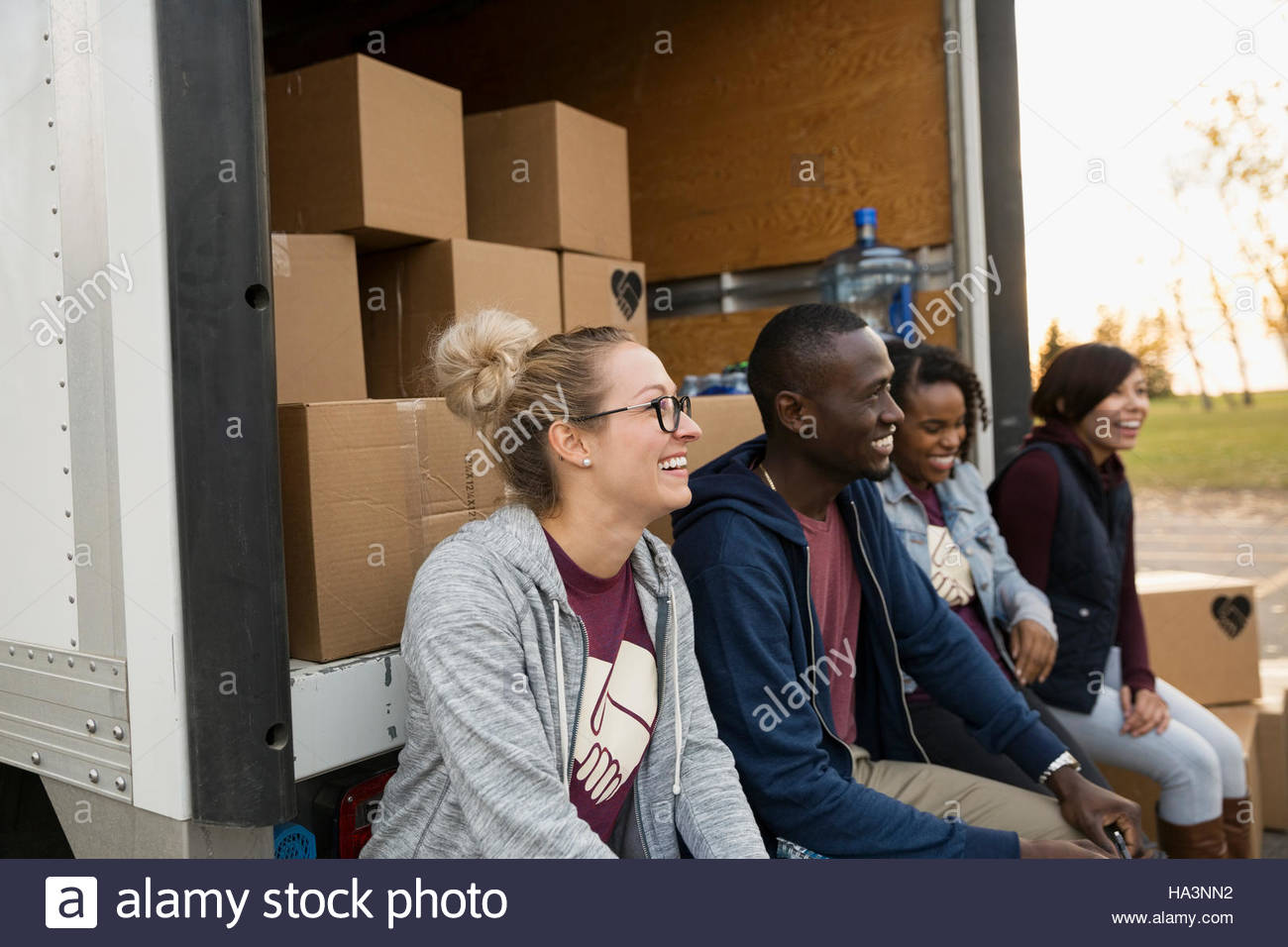 Smiling volunteers sitting at back of truck with cardboard boxes - Stock Image