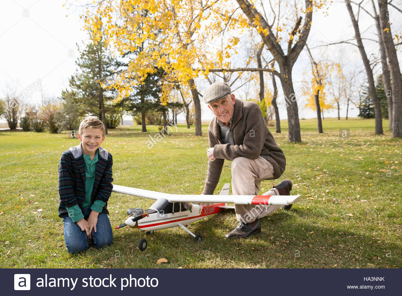 Portrait grandfather and grandson with model airplane in autumn park - Stock Image