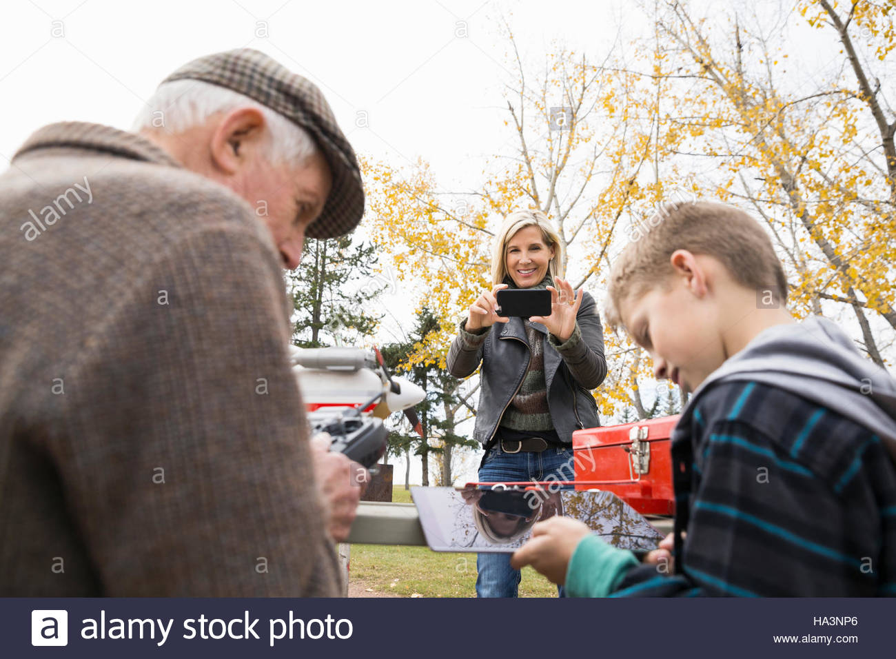 Senior man and grandson with model airplane remote control and digital tablet in park - Stock Image
