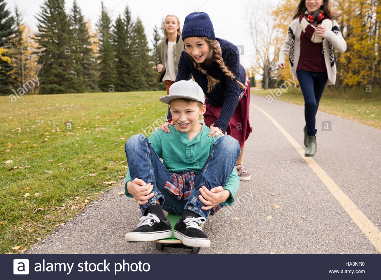 Tween boy and girls skateboarding on path in autumn park - Stock Image