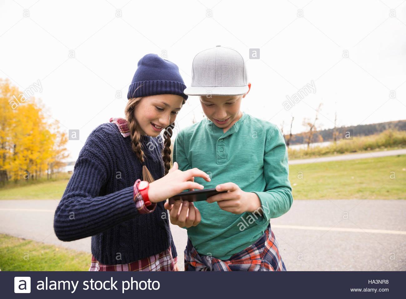 Tween boy and girl texting with cell phone in autumn park - Stock Image