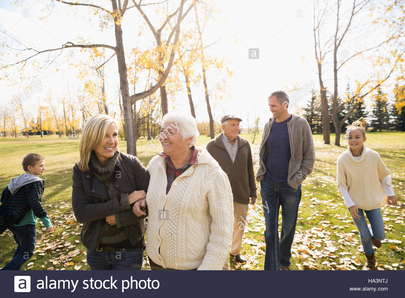 Multi-generation family walking in sunny autumn park - Stock Image