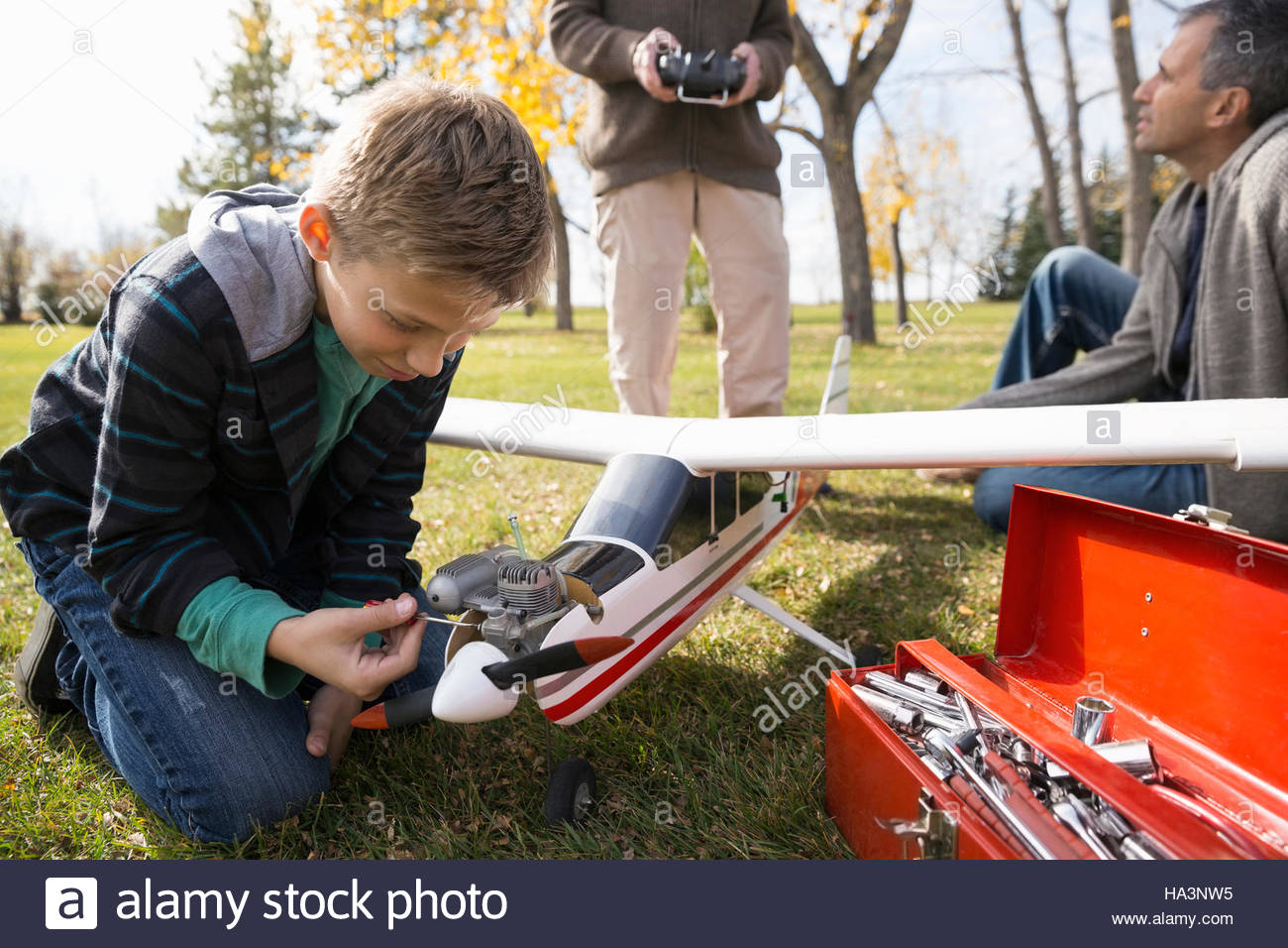 Boy fixing model airplane with father and grandfather in park - Stock Image