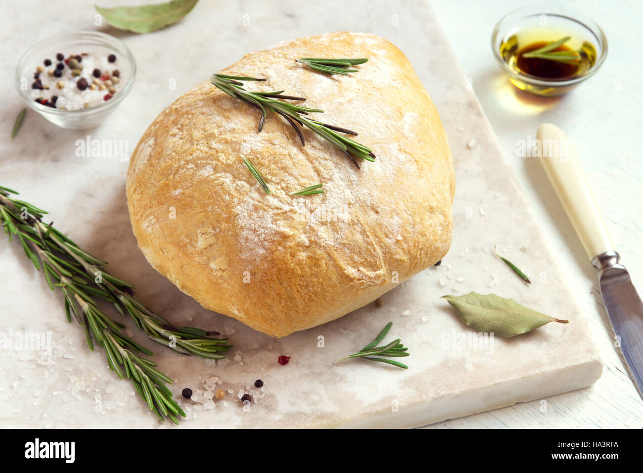 Fresh ciabatta bread with rosemary and extra virgin olive oil on rustic white background - Stock Image