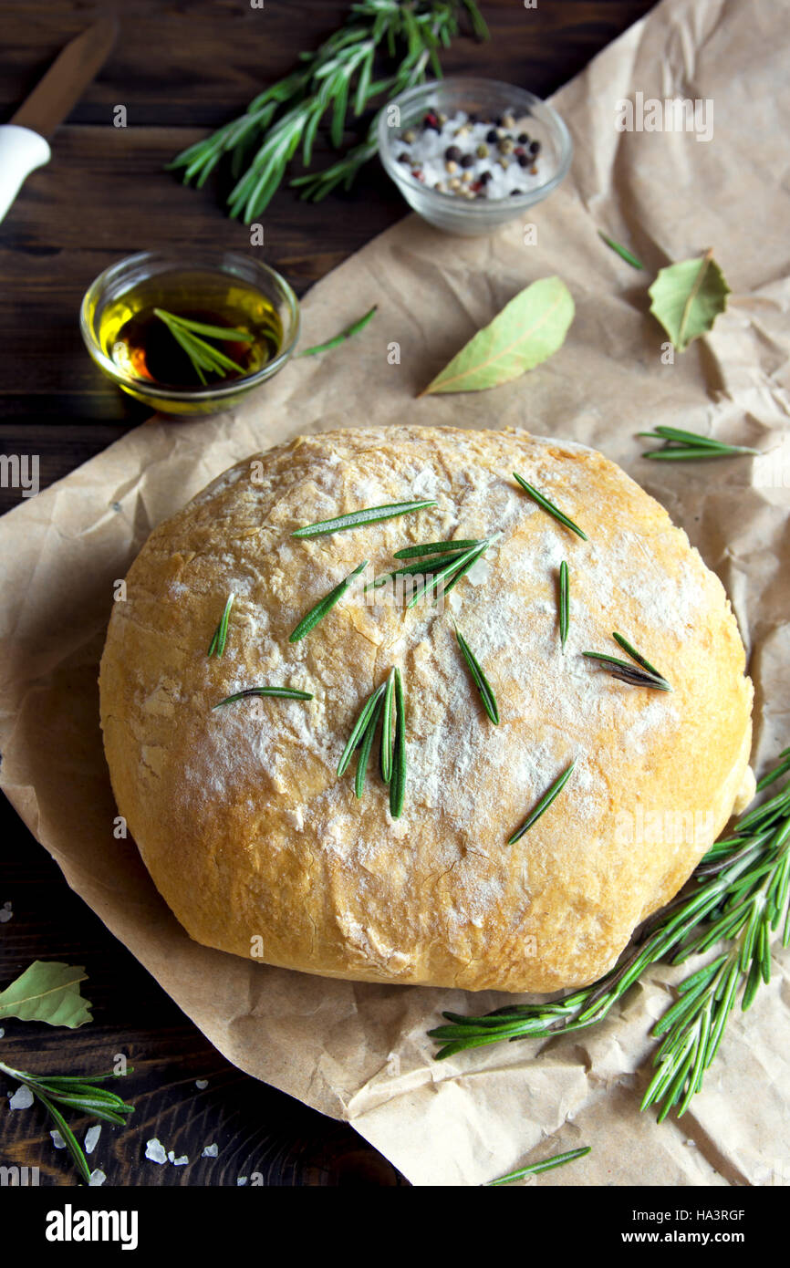 Fresh homemade ciabatta bread with rosemary and extra virgin olive oil on rustic wooden background - Stock Image