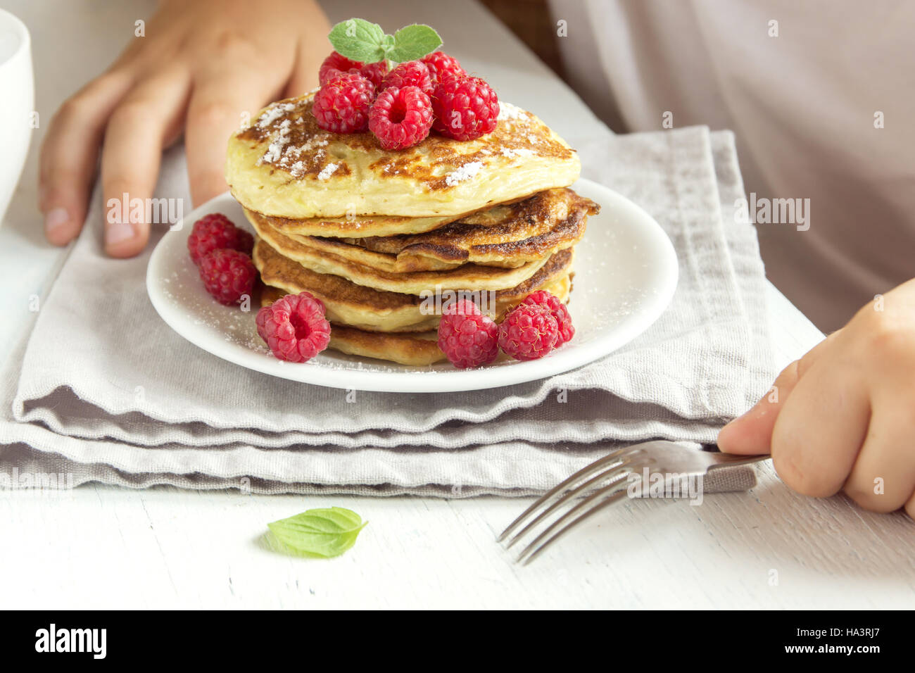 Child eating healthy breakfast at home - pancakes with raspberries on plate with children hands - Stock Image
