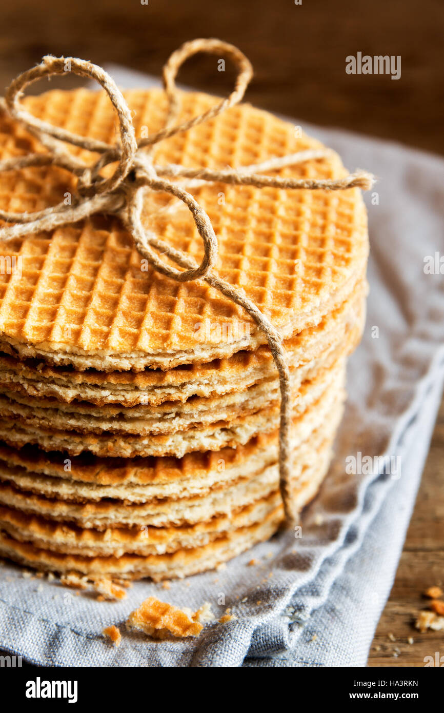 Stack of traditional dutch caramel waffles tied up with jute twine on rustic wooden background, selective focus - Stock Image