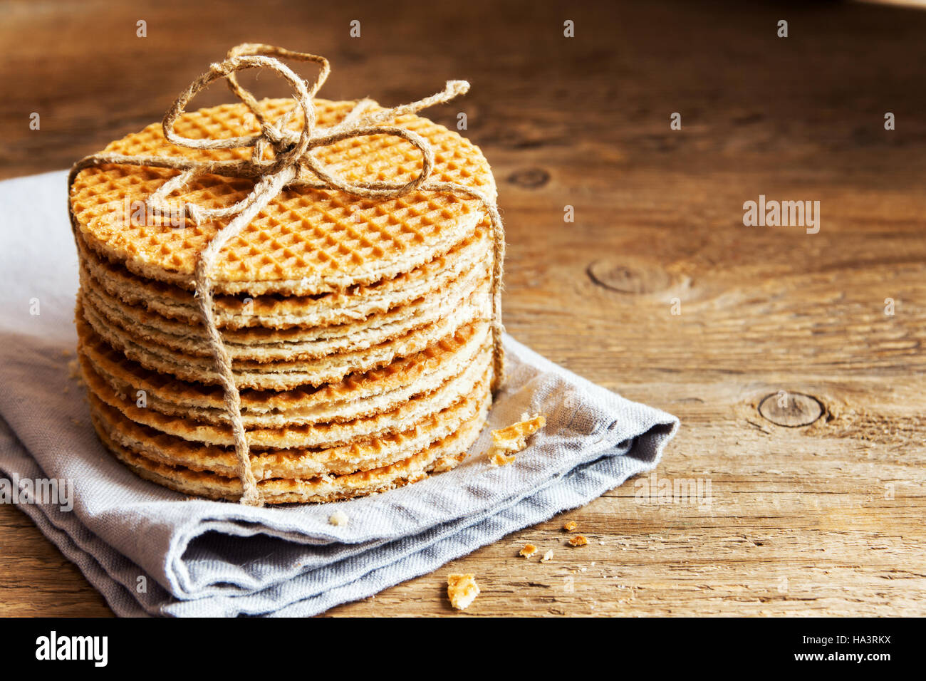 Stack of traditional dutch caramel waffles tied up with jute twine on rustic wooden background, copy space, selective Stock Photo
