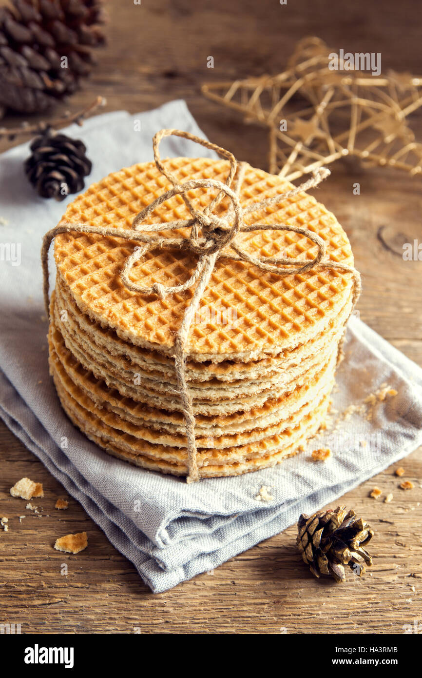 Stack of traditional dutch caramel waffles tied up with jute twine on rustic wooden background with Christmas decor - Stock Image