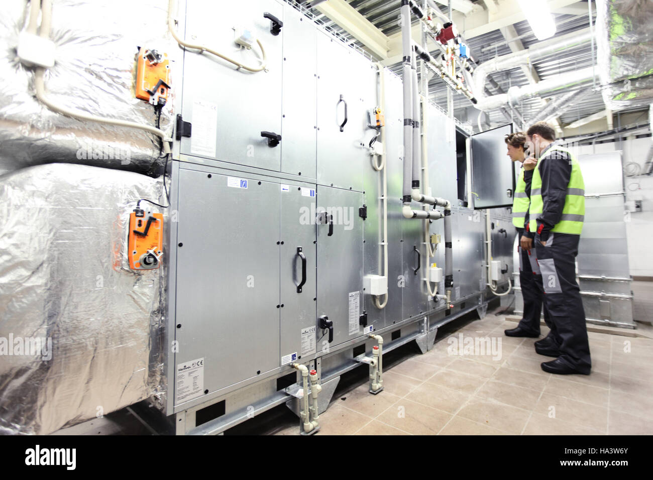 Two workers check switchboards at factory auxiliary room - Stock Image