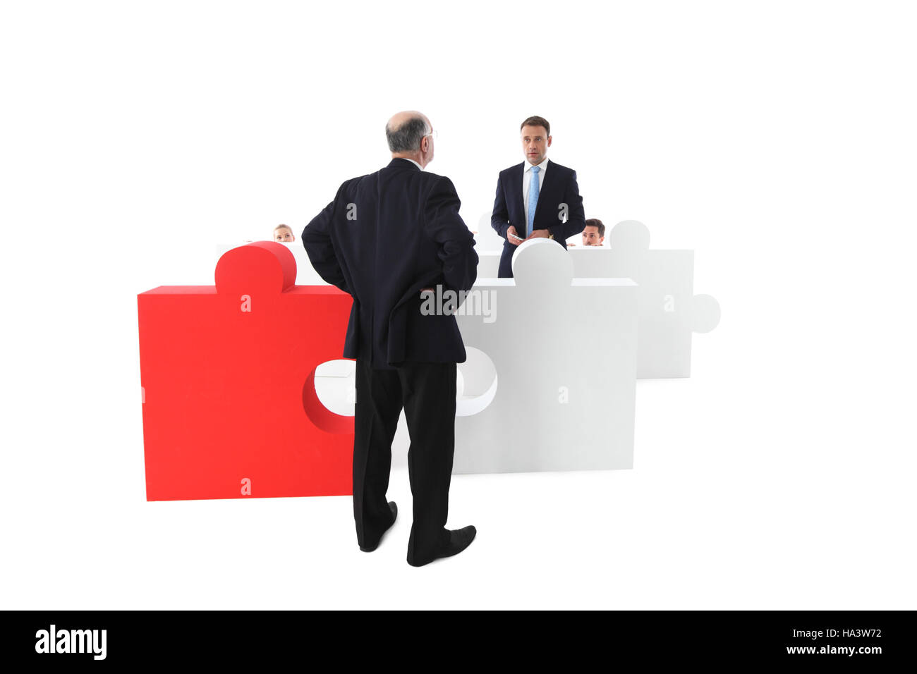 Confused shocked, surprised worker apologizes to manager, part of puzzle team concept, isolated on white - Stock Image