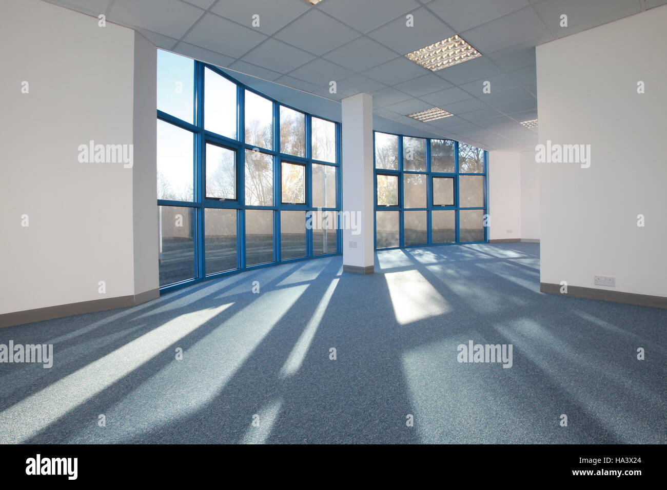bright sunlit empty office space with sunlight streaming through windows - Stock Image