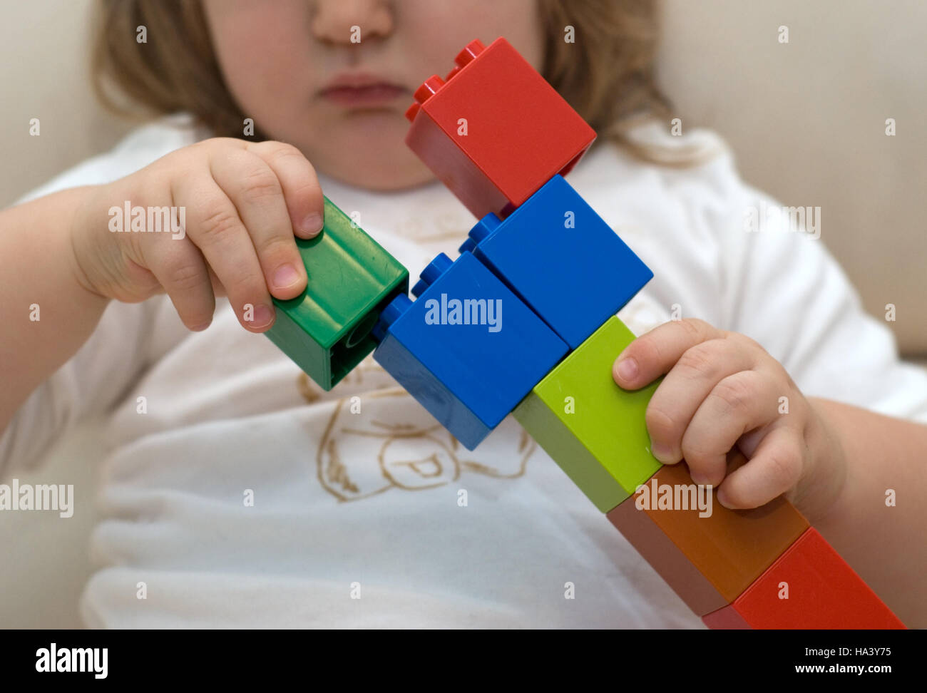 Baby's hands with building kit - Stock Image