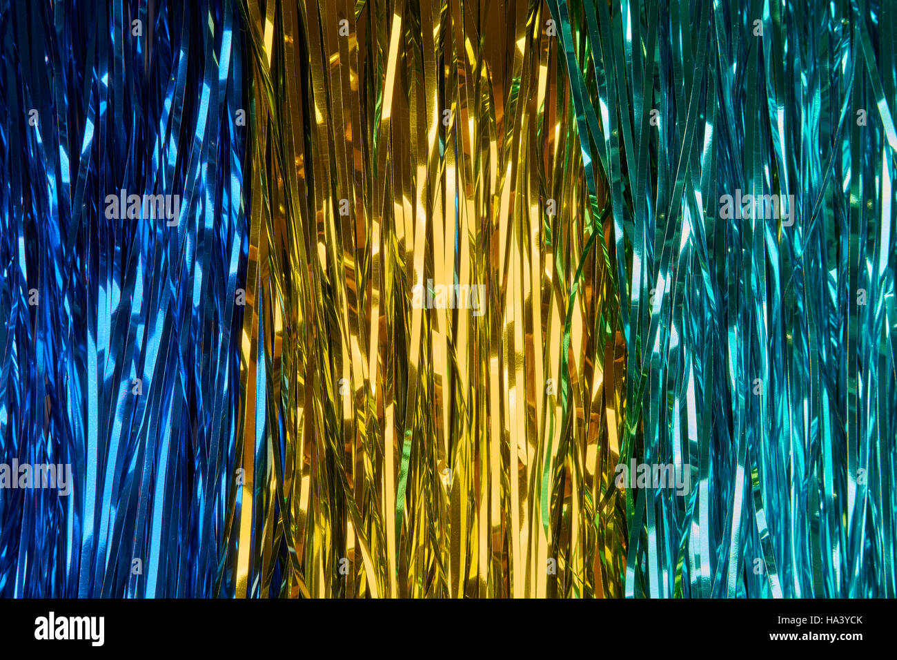 Christmas background with blue, yellow and green tinsel - Stock Image