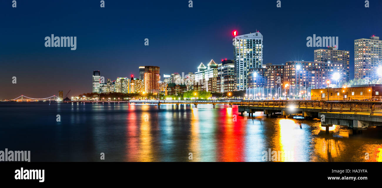 Jersey City skyline panorama by night, reflected in Hudson River, with Verrazano–Narrows Bridge in the background - Stock Image