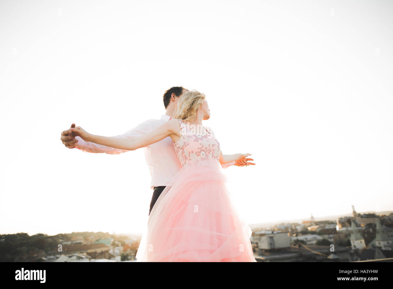 Young couple in love posing on roof with perfect city view holding hands and hugging . Beautiful sunset - Stock Image