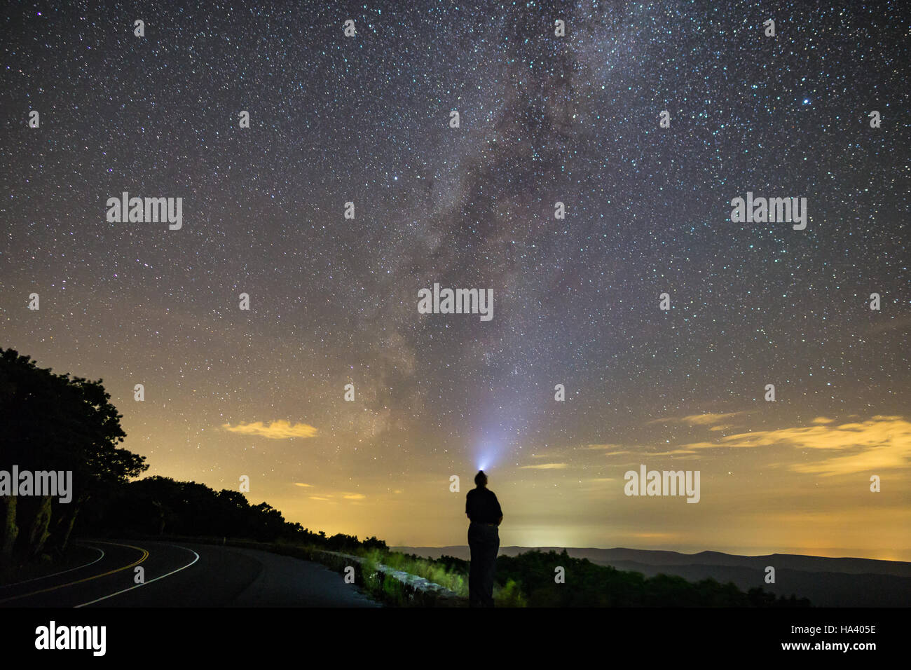 Galactic Selfie. A single, lone person stands staring up at the stars in the night sky along with the Milky Way - Stock Image