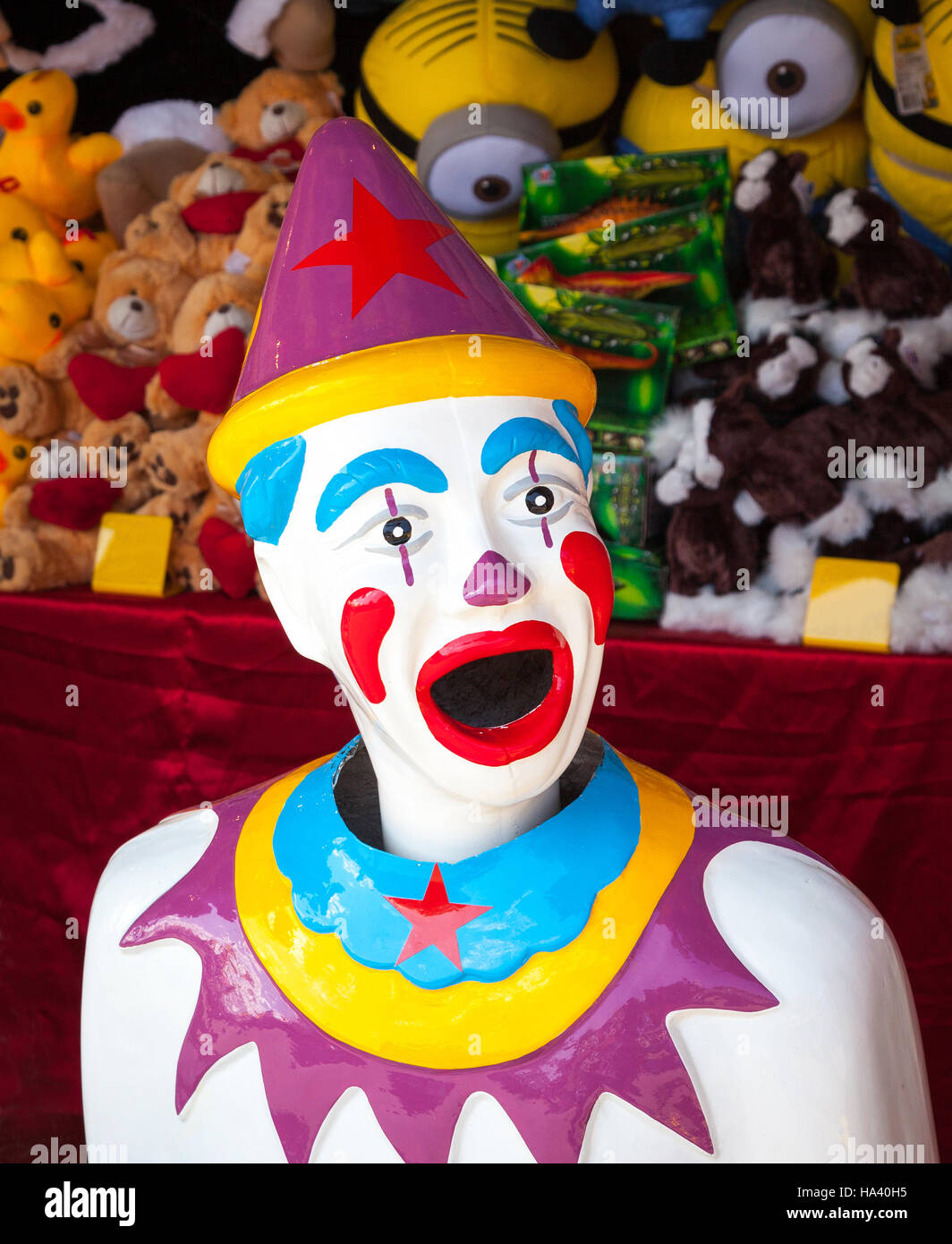 A colorful arcade clown with prizes stacked behind him. - Stock Image